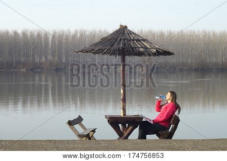 Beautiful young woman rests by the river Danube in Serbia and drinks water under the sunshade