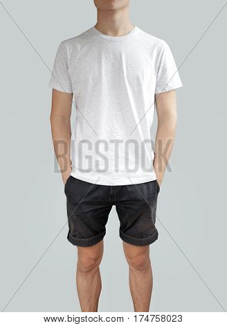 White T Shirt And Black Shorts On A Young Man Template On Grey Background. Hands In Pockets.