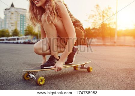 Beautiful young girl with tattoos riding on his longboard on the road in the city in sunny weather. Extreme sports. Close up
