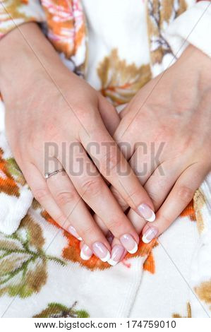 French manicure. wedding ring on the finger