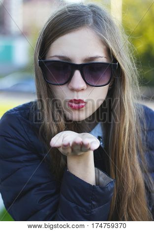 Young atractive beautiful woman in black sunglasses showing air kiss.