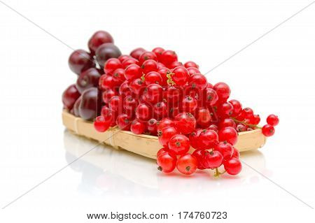 Ripe red currant berries and cherries in a basket on a white background. horizontal photo.