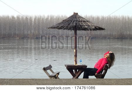 Beautiful young woman rests in nature by the river Danube in Serbia and drinks mineral water under the sunshade