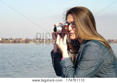 Young woman with vintage retro film camera takes photos on the bank of  the Danube river near Novi Sad in Serbia.