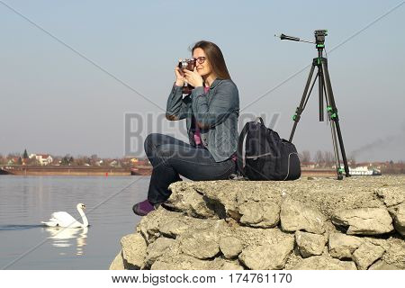 Young woman with vintage retro film camera takes photos on the bank of  the Danube river in Serbia.