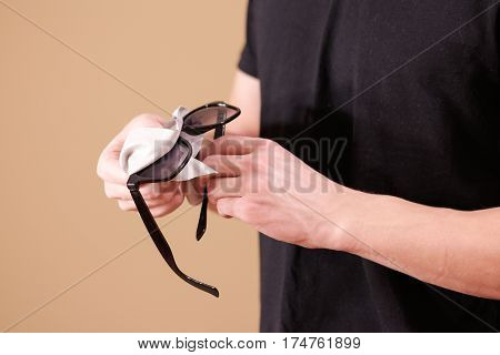 Man Hand Cleaning Black Sun Glasses Lens With Isolated Background