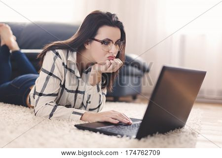 Woman searching for boys online on laptop indoor