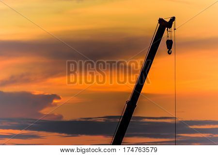 mobile crane arm operating silhouettes at sunset