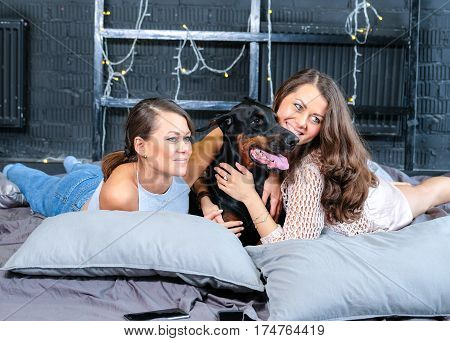 Woman in bed with big black doberman dog