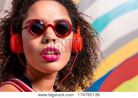 Portrait of face of calm female with bright makeup wearing sunglasses and hearing song thorough headset