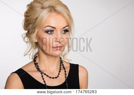 Charming blonde with a stylish hairstyle on the gray background