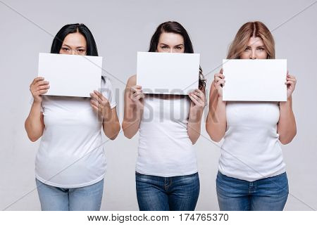 Do not mute us. Different good looking determined women holding up white signs covering half of their faces while working on a new social campaign