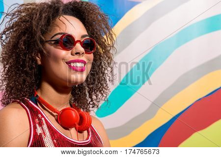happy female with radiant makeup wearing sunglasses. She is standing and smiling. Copy space