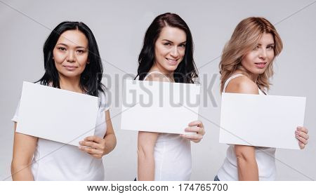 All together. Lovely cute diverse ladies holding up pieces of paper while smiling and posing for a photographer in a studio