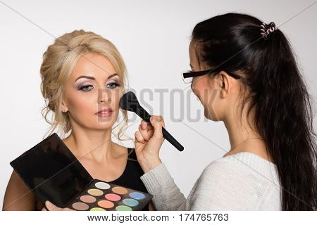 Make-up artist doing make-up of a beautiful young girl in the studio