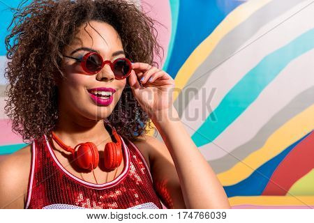 Portrait of cheerful woman with bright look and headset. Copy space on colorful background