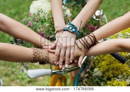United hands of young females. Stylish girlfriends in boho hippie bracelets near bicycle handlebar, top view. Togetherness and support, youth fashion and active lesiure. Women friendship