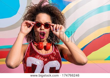 Screaming african female with curly hair wearing sunglasses near painting wall