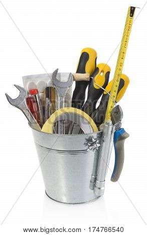 Handyman tool set: screwdrivers wrenches tape pliers measuring tape flashlight. DIY kit set in a silver bucket isolated on white background with light shadow and reflection.