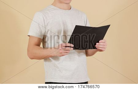 Man Holding Black A4 Paper. Read Booklet. Leaflet Presentation. Pamphlet Hold Hands. Man Show Clear