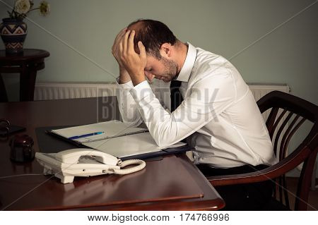 tired business man sitting at table in office