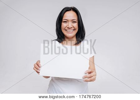 Smile is your best response. Unique wonderful bright lady holding up a white sign while wearing casual clothes accentuating her natural beauty
