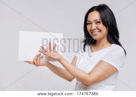 Important message. Cute classy petite woman holding a blank sheet of paper and pointing at it with her hand while posing in casual clothes