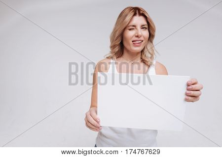 Why so serious. Remarkable artistic attractive woman goofing around on set while making funny faces and holding a white sign in her hands