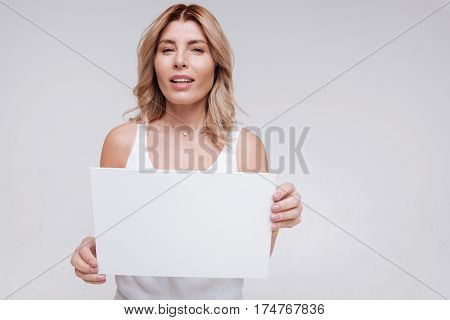 Transmitting a message. Hypnotic curvy devoted woman demonstrating white piece of paper while working during a photoshoot advertising natural beauty