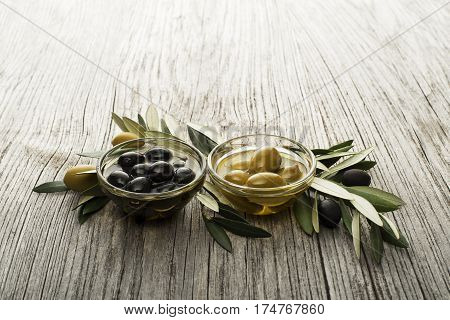 Olive oil with fresh olive fruits on wooden background.