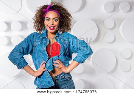 Waist up portrait of Cheerful young female with blue eye makeup dressing in retro style. She is standing and posing. Copy space