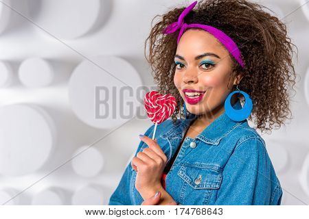 Portrait of Happy young female with bright makeup holding candy in hand. Copy space