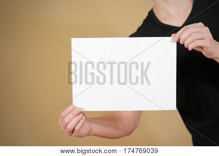 Man In Black T Shirt Holding Blank White A4 Paper. Leaflet Presentation. Pamphlet Hold Hands. Man Sh