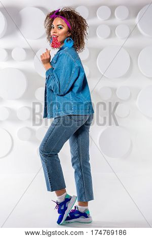 Full length portrait of happy african female with bright look and wearing in sporty clothes eating candy