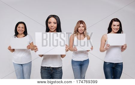Expressing our desires. Charismatic motivating pretty ladies wearing same clothes and holding up the same signs while posing for a professional photographer