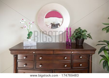 Beautiful Dresser and Mirror Against a Wall in a Home.