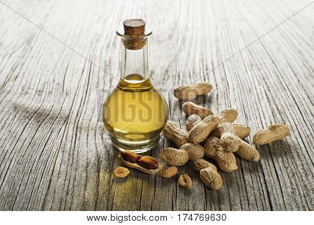Peanut oil in a glass bottle on a wooden background