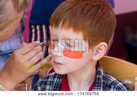 Child animator, artist's hand draws face art painting to little boy. Painter makes tiger eyes on kid. Children holiday, event, birthday party entertainment.
