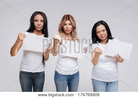 Join us in our fight. Gorgeous confident resolute ladies pretending protesting together against something while posing in a studio clenching their fists