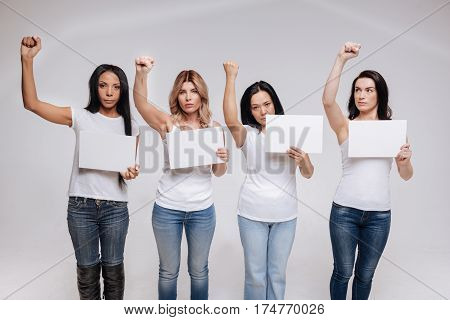 We change everything together. Wonderful modern passionate women standing united isolated on white background wearing similar clothes and striking a similar pose