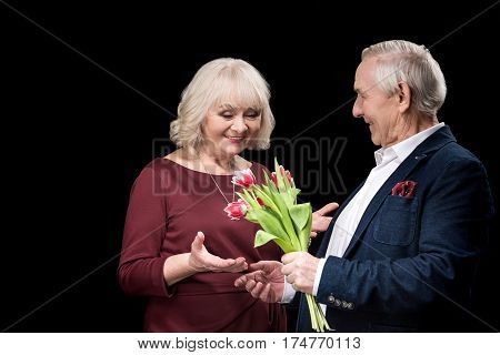 Smiling senior man presenting tulips bouquet to happy woman international womens day concept