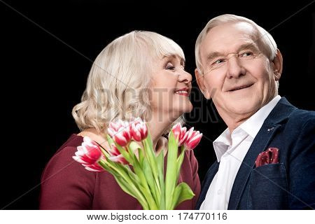 Happy senior couple with tulips bouquet on black international womens day concept