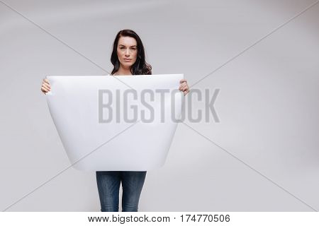 Serious matter. Hypnotic daring brave activist looking very serious while posing for a new social campaign and holding a blank poster