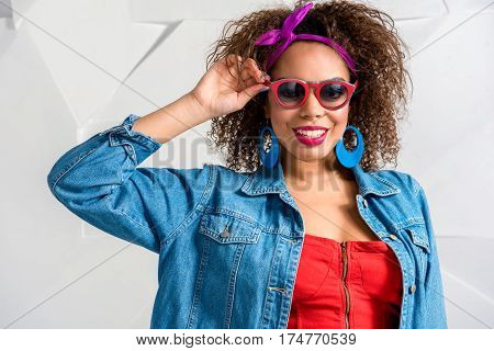 Cheerful african female holding sunglasses and smiling. She wearing in bright clothes
