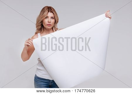 This matters. Committed graceful serious lady taking part in a new social campaign while posing for a photographer holding a poster