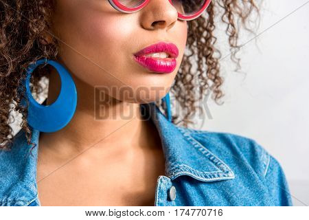Close up of Calm young woman with pink shade of lipstick wearing bright accessory