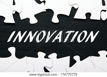 The word Innovation in white text on a blackboard with a border of jigsaw puzzle pieces