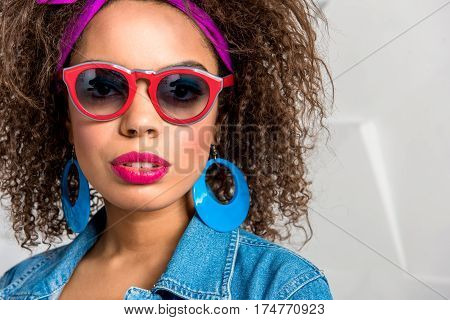 Portrait of serene african female expressing her desire. She is wearing bright sunglasses and big earrings. Copy space