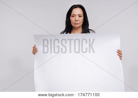 Do not miss this sign. Ambitious strong modern lady holding a blank poster while standing isolated on white background and expressing frustration