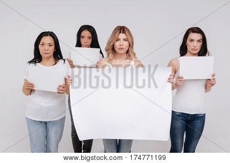 We are not silent. Magnificent fearless young ladies pretending marching against some social injustices while holding posters and standing isolated on white background